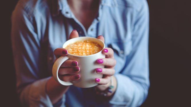 コーヒーカップを持つ女性の手元の画像