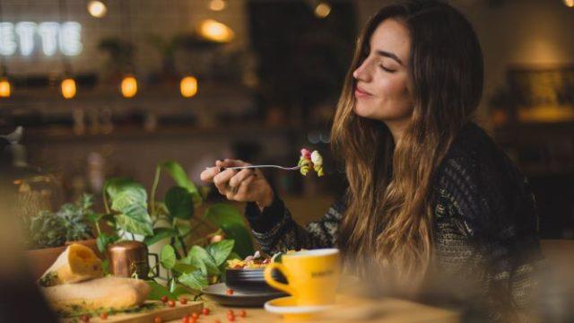 女性が美味しそうに食事をしている画像