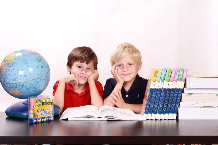 仲良く机に向かって勉強する男の子二人の画像