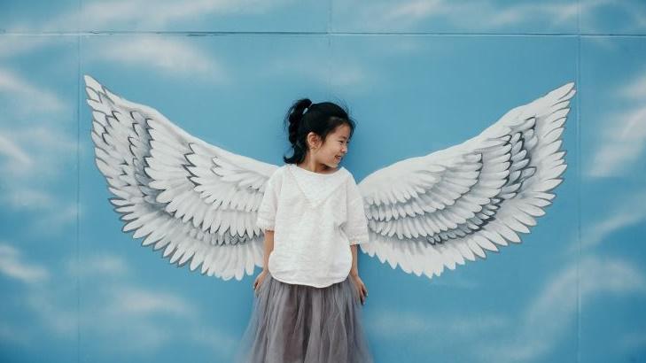 天使の羽が描かれた壁画の前に立つ女の子の画像