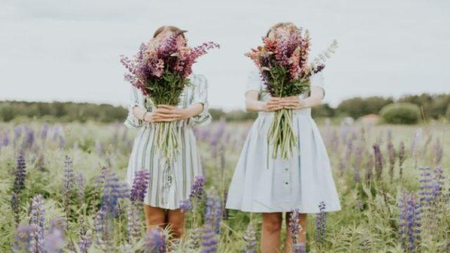 草原に佇み花束を持つ二人の少女の画像