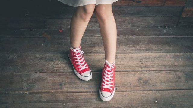 赤いスニーカーを履いた少女の足元の画像