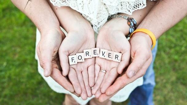 FOREVERと書かれたパズルを手のひらに乗せているカップルの手元の画像