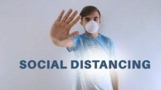 「social distancing 」の掲示板の前でストップのジェスチャーをするマスク姿の男性の画像