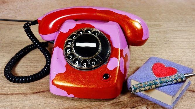 赤い電話と赤いハートが書かれた表紙の手帳の画像