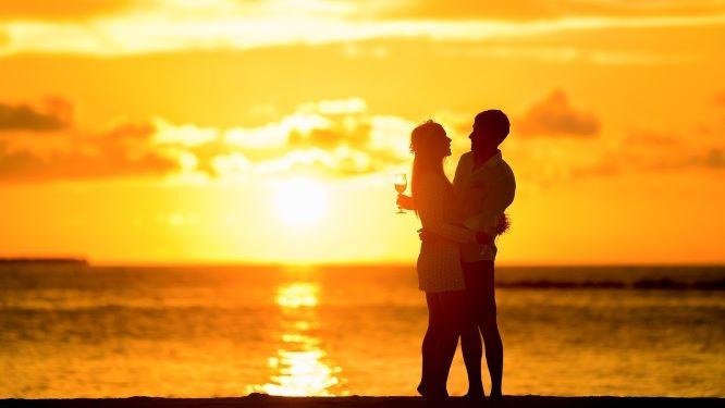 夕日が沈むビーチで寄り添うカップルの画像