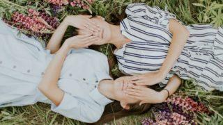 二人の姉妹が草原に寝転んでいる画像