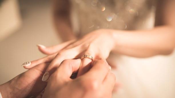 新婦の指に指輪をはめる新郎の画像
