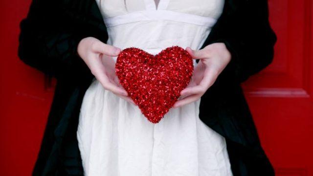赤いハートのクッションを持つ女性の手元の画像