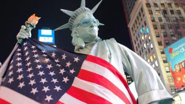 ニューヨークタイムズスクエアで自由の女神の扮装で星条旗を持つ人の画像