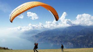 山上でパラグライダーで飛ぶ準備をする人の画像