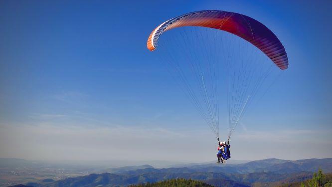 パラグライダーで飛んでいく二人の画像