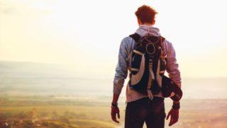 山の頂から風景を望む男性の後ろ姿