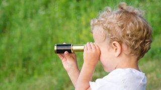 望遠鏡を覗き込む男の子