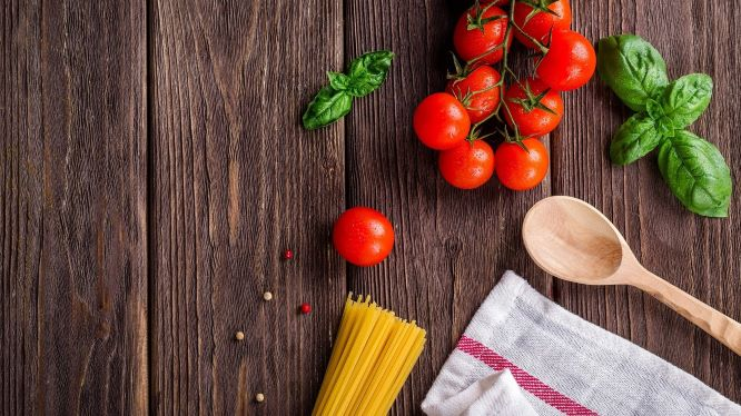 テーブルの上に置かれたパスタとミニトマトなどの食材