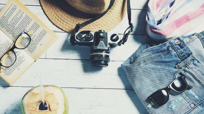 机の上に置かれたカメラや帽子などのレジャー用品