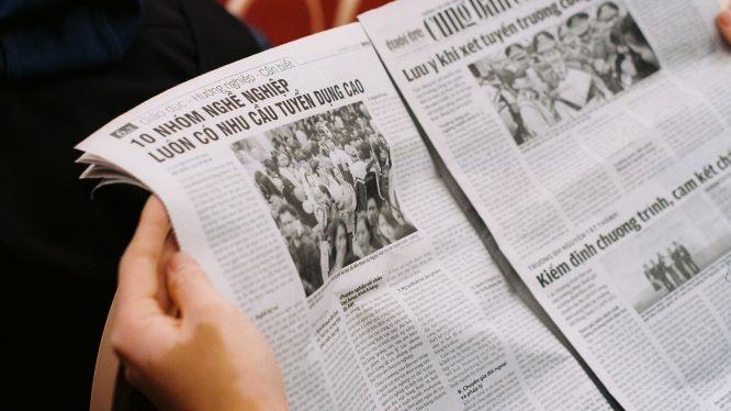 新聞を広げて読んでいる人の手元